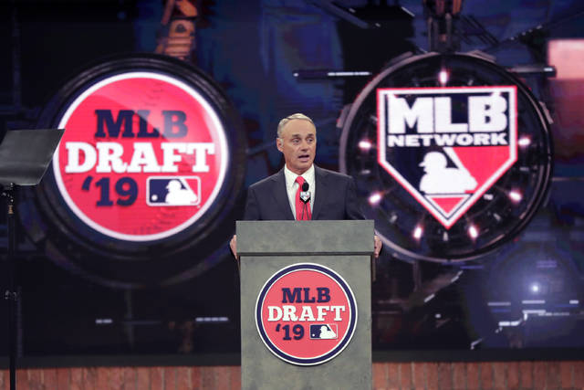 FILE - In this June 3, 2019, file photo, Baseball Commissioner Rob Manfred speaks during the first round of the baseball draft in Secaucus, N.J. Baseball's amateur draft this week will look much different because of the coronavirus pandemic, and more permanent changes could be coming soon. (AP Photo/Julio Cortez, File)