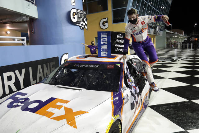 Denny Hamlin jumps from his car after winning a NASCAR Cup Series auto race Sunday, June 14, 2020, in Homestead, Fla. (AP Photo/Wilfredo Lee)