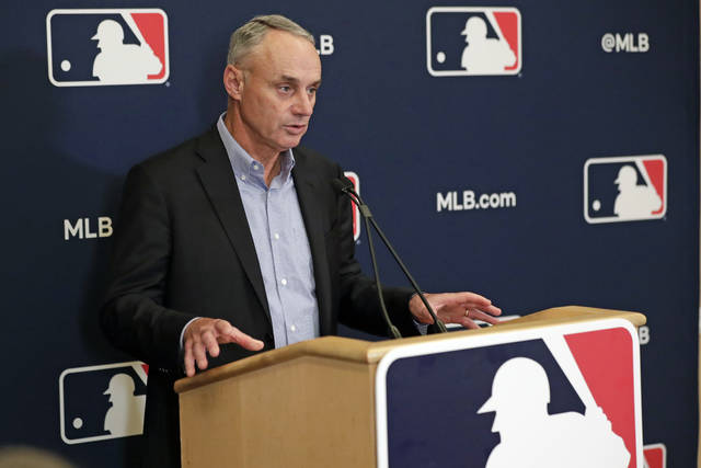 "FILE - In this Feb. 6, 2020, file photo, Baseball Commissioner Rob Manfred answers questions at a press conference during baseball owners meetings in Orlando, Fla. Manfred tells The Associated Press that the commissioner's office, teams and the players' association ""owe it to our fans to be better than we've been the last three months."" (AP Photo/John Raoux, File)"