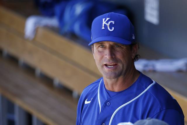 "FILE - In this March 9, 2020, file photo, Kansas City Royals manager Mike Matheny pauses in the dugout prior to a spring training baseball game against the Arizona Diamondbacks in Scottsdale, Ariz. Forget about those halcyon first few days of spring training, when arranging for the right tee time on the right golf course is often more challenging than the work on the field. When major leaguers report next week for spring training 2.0 — or perhaps more accurately, baseball's first summer camp — time will be one precious commodity with about three weeks before opening day. ""We're going to have some live batting practices the first day they show up. Day 1 and Day 2. ... Multiple ups for the starters,"" Matheny said Friday, June 26, 2020, on a video conference call. ""These guys are prepared for that. They've been hungry for it."" (AP Photo/Ross D. Franklin, File)"
