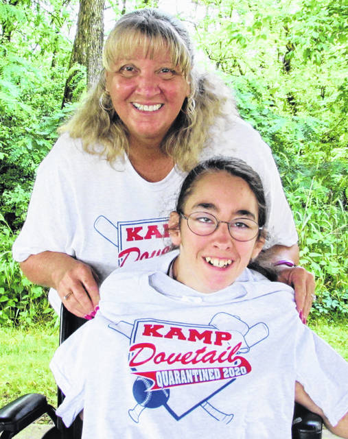 SATH Executive Director Linda Allen displays the one-of-a-kind T-shirts that each camper who would've attended this year's canceled KAMP Dovetail will receive. Also shown is her close friend Heather Porter, whom Allen said was a 13-year veteran of the annual event for special needs children.