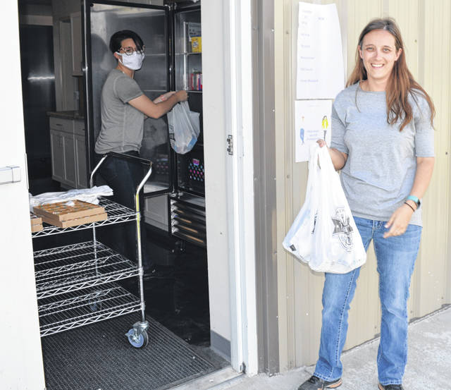 "Christina Ewing picks up meals for her children in East Clinton Local School's ""Seamless Summer Option"" free meal program."