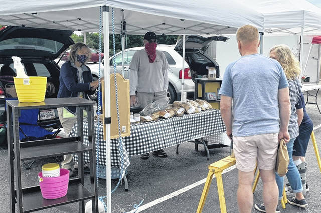 The Clinton County Farmers Market continued Saturday at its new current home at the Clinton County Fairgrounds with social distancing and other precautions. The market continues at the fairgrounds 9 a.m.-noon Saturdays during the summer. Visit www.clintoncountyfarmersmarket.com for weekly vendor participation information and pre-ordering options, payment methods, and ordering deadlines. Shown is the booth for Ogden Acres.
