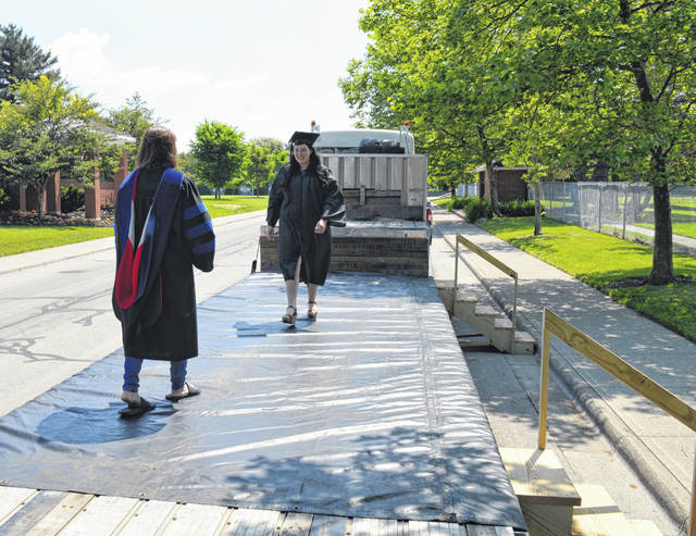 Samantha Harter, facing camera, walks on her father's flatbed trailer to receive her Wilmington College diploma from WC Associate Professor of Communication Arts and Agriculture Dr. Corey Cockerill.