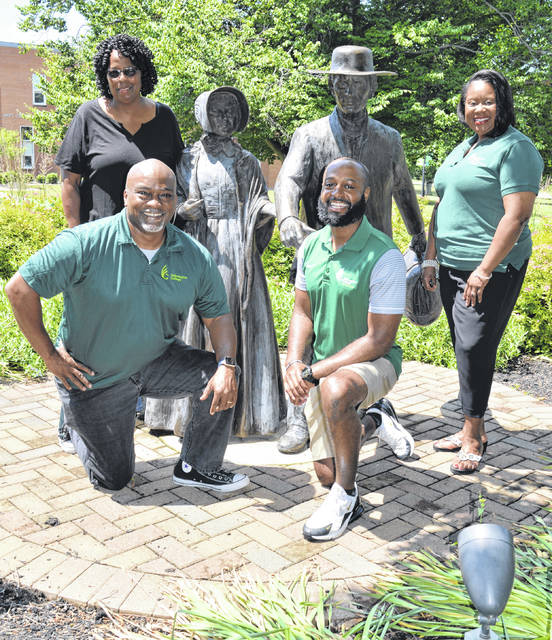 Four Wilmington College colleagues meet around statues on campus that recall an action done in 1862 by Clinton Countians Isaac and Sarah Harvey in support of emancipation for slaves. From the left foreground going clockwise are Director of Diversity & Inclusion Chip Murdock, Director of Career Services Dr. Nina Talley, Vice President of Student Affairs and Dean of Students Sigrid Solomon, and Men's Basketball Associate Head Coach Micah Mills.