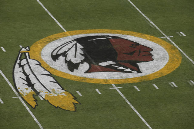 "FILE - In this Aug. 7, 2014, file photo, the Washington Redskins logo is seen on the field before the team's NFL football preseason game against the New England Patriots in Landover, Md. Washington's NFL team will get rid of the name ""Redskins"" on Monday, July 13, according to multiple reports. It's unclear when a new name will be revealed for one of the league's oldest franchises. The team launched a ""thorough review"" of the name July 3. (AP Photo/Alex Brandon, File)"