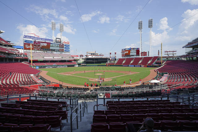 Cincinnati Reds players take the field for an intra-squad game during team baseball practice at Great American Ballpark in Cincinnati, Sunday, July 5, 2020. (AP Photo/Bryan Woolston)