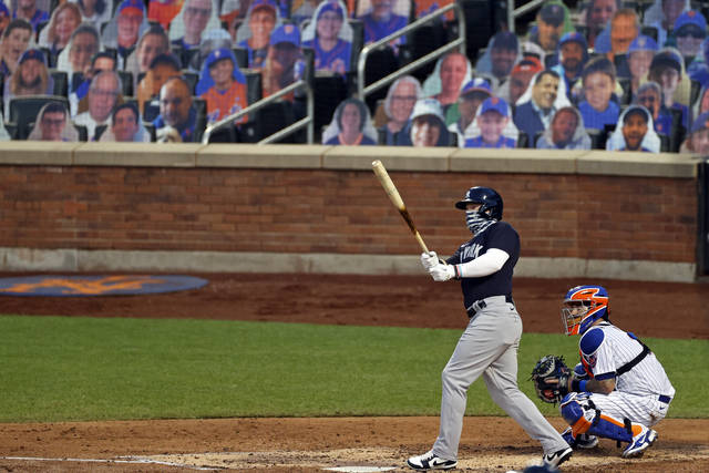 New York Yankees' Clint Frazier, left, watches his two-run home run against the New York Mets during the fourth inning of a baseball spring training game Saturday, July 18, 2020, in New York. (AP Photo/Adam Hunger)