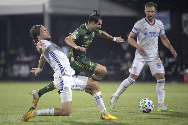 Portland Timbers midfielder Diego Valeri is separated from the ball by FC Cincinnati defender Tom Pettersson, left, as midfielder Caleb Stanko (33) watches during the second half of an MLS soccer match Tuesday, July 28, 2020, in Kissimmee, Fla. (AP Photo/Phelan M. Ebenhack)