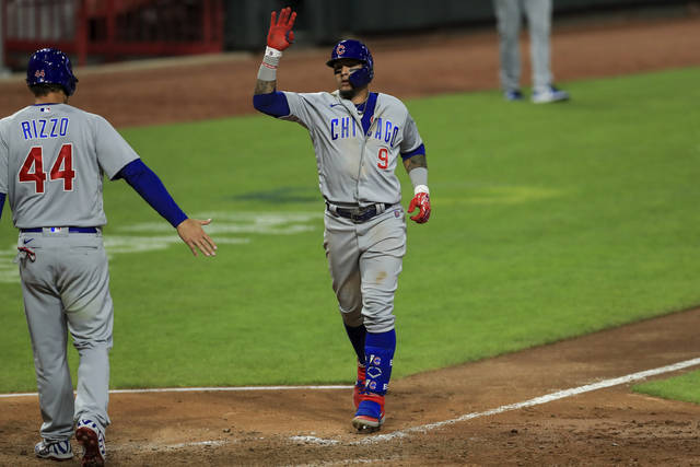 Chicago Cubs' Javier Baez (9) reacts with Anthony Rizzo (44) after hitting a two-run home run in the ninth inning during a baseball game against the Cincinnati Reds in Cincinnati, Tuesday, July 28, 2020. (AP Photo/Aaron Doster)