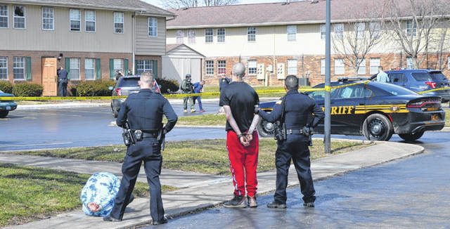 Teddy Knapp is led out in handcuffs by Wilmington officers during the March incident. Arrested earlier were Jennifer Roush (crouching at left) and Brandon King (in red sweatpants). In the upper left of the photo is the window through which tear gas canisters were fired.