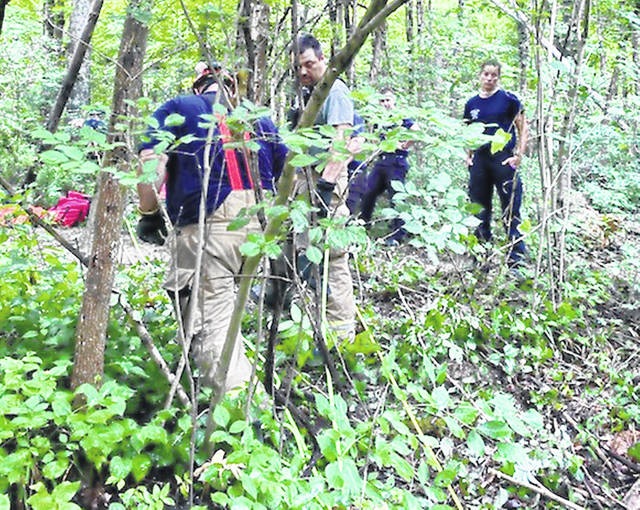 Rescue personnel are pictured Thursday using ropes to pull a victim to safety after an accident at the Fallsville Wildlife Area.