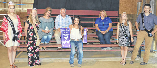 The Grand Champion Pen of 3 Chickens exhibited by Bradeanna Arehart (sitting in the center foreground) of the Wilmington area brought a premium of $1,580. The buyers are ATSG (Air Transport Services Group), American Equipment Service, Arehart-Brown Furneral Services LLC, BMR Farm, Bentley Pig Sale, Bush Auto Place, Cherrybend Pheasant Farm / Ellis Farms, Clinton County Board of Realtors, D & E Equipment Co., Doug Rinehart, Alexander-Gerber Crop Insurance, Groves Tire & Service, Johnson Farms, Loads 2 Roads, Lowes, McCarty Gardens, Merchants National Bank, American Legion Post 49, Miller Farms & Trucking, Bill and Tonya Ostermeier, Panetta Excavating Inc., Peoples Bank, Chris and Brooke Stingley, Sunrise Cooperative, Tro Go Amish Recipe Pretzels and Doughnuts, WyldFyre Farms, Mary Beth and Terence Habermehl, and Auctioneer Harley Jackson.