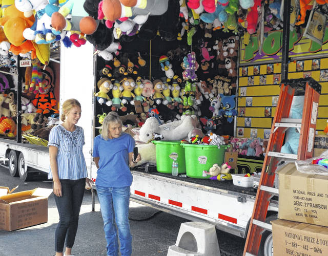 A few game booths had arrived in town by Monday for the upcoming Clinton County Fair. From left are fairground office workers Katie Hughes and Teresa Webb as they look at a photo Webb just took of a stuffed toy goat she will be sending to a local person interested in the agriculture industry.
