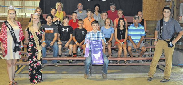 The Reserve Champion Meat Fryer Chicken exhibited by Henry Hildebrandt (seated in center foreground) went for a $1,750 premium at the Junior Fair Sale of Champions. The buyers are Accurate Soils, Autumn Years Nursing Center, Cherrybend Pheasant Farm / Ellis Farms, Croghan Trucking / Tom Rayburn Memorial, Nutrien Ag Solutions, D'Shealy Designs, DeBold Builders, Doug Rinehart, Marci and Mitchell Ellis, Farm Credit Services, Alexander-Gerber Crop Insurance, Groves Tire & Service, Healthsource of Ohio, Ag-Pro, Johnson Farms, Bill Marine Ford, Steve and Roseanne McKay, Merchants National Bank, American Legion Post 49, Paul Hall & Associates - Justin Holbrook, Hannah and Jacob Scott, Smith Farms Trucking, Brady and Donna Snyder, Ron Trusty Insurance, Vital Fitness, Murphy Farms, Murphy Family, Houston's HVACR (Heating, Venting, Air Conditioning, & Refrigeration), and the Bennett Family.