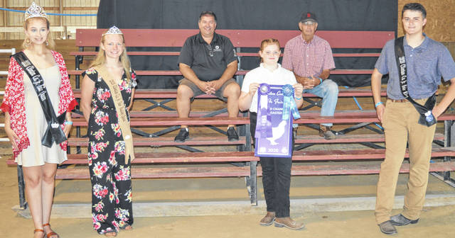 The Grand Champion Meat Roaster Chicken exhibited by Madison Taylor (center foreground holding a sign and ribbons) of the Midland area received a premium of $575 at the Clinton County Junior Fair Sale of Champions. The buyers are American Equipment Service, BDK Feed & Supply, Bronson Door Co., Chester Herdsmen 4-H Club, Groves Tire & Service, Heeg Farms, Johnson Farms, Liberty Savings Bank, Paul Hall & Associates / Justin Holbrook; Leilani Popp, Wilmington Auto Center - Chrysler, Dodge, Jeep, the Wilmington Savings Bank, Phyllis Cocklin, Chris and Miranda Hilderbrandt, Keltner Family Farm, and the McEvoy Family.
