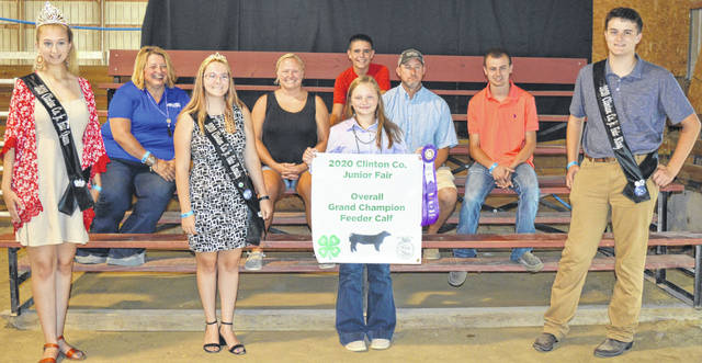 The 581-pound Overall Champion Market Feeder Calf exhibited by Taylor Barton (in foreground holding sign and ribbon) of the Sabina area collected a $3,130 premium. The buyers are Agrigold Hybrids, American Equipment Service, Barton Farms, Belles Farm Animal Veterinary Services, Bronson Door Co., Cherrybend Pheasant Farm / Ellis Farms, Nutrien Ag Solutions, Chad and Alison Davis Family, DeBold Builders, Marci and Mitchell Ellis, Farm Credit Services, Flint Concessions, Groves Tire & Service, Hartley Oil Co., Keri and Alex Hodson, J & L Farms, Ag-Pro, LGSTX Services Inc., McCarty Gardens, Merchants National Bank, Milled Right Inc., Connie Miller, Rob's Equipment, Schneder Farms, Hannah and Jacob Scott, Skyline Chili in Wilmington, Smith Farms Trucking, Southern Hills Community Bank, Sunrise Cooperative, Ron Trusty Insurance, Wilmington Lions Club, Wilmington Savings Bank, Matt Younker, Jack and Cindy Anderson, Susan Ross, Pioneer Seeds, John and Alex Caney, Nick Anderson, and the Wesley Anderson Family.