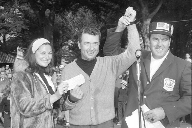 FILE - In this  Jan. 31, 1966, file photo, John Keane, right, general chairman of the Lucky International Golf Tournament, raises the hand of Ken Venturi after presenting him with the winners check of $8,500 at Harding Park in San Francisco, Calif. Helping Ken hold the check is his wife, Connie. The PGA Tour made an annual stop at Harding Park in the 1960s, and it produced a pretty stout roll call of champions. The most popular winner was Venturi, who grew up in San Francisco playing the municipal course. (AP Photo/File)