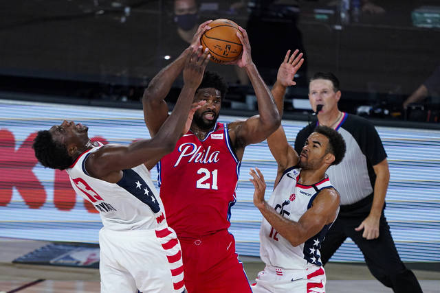 Washington Wizards center Thomas Bryant (13) and guard Jerome Robinson (12) tries to tie up Philadelphia 76ers center Joel Embiid (21) during the second half of an NBA basketball game Wednesday, Aug. 5, 2020 in Lake Buena Vista, Fla. (AP Photo/Ashley Landis)