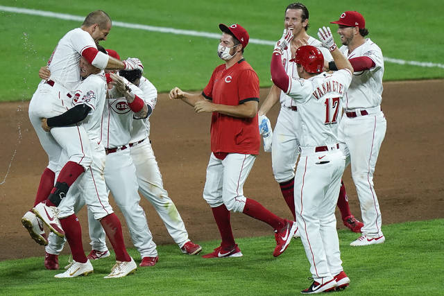Cincinnati Reds teammates celebrate after defeating the Kansas City Royals in a baseball game at Great American Ballpark in Cincinnati, Tuesday, Aug. 11, 2020. (AP Photo/Bryan Woolston)