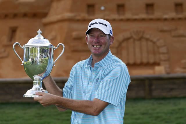 Jim Herman holds the championship trophy after winning the final round of the Wyndham Championship golf tournament at Sedgefield Country Club on Sunday, Aug. 16, 2020, in Greensboro, N.C. (AP Photo/Chris Carlson)