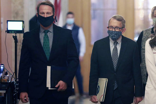 FILE— In this file photo from April 15, 2020, Ohio Lt. Gov. Jon Husted, left, and Gov. Mike DeWine, walk into their daily coronavirus news conference at the Ohio Statehouse in Columbus, Ohio. Husted, a former University of Dayton football player, has been advocating that fall high school sports proceed during the coronavirus pandemic. He tweeted Aug. 10 that good results can't be expected when sports are taken away from young people. Husted's comments come as Gov. DeWine is expected to announce his plans for sports on Tuesday, Aug. 18, 2020. (Doral Chenoweth/The Columbus Dispatch via AP)