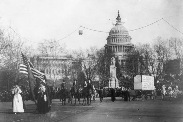 "In this circa 1913 photo made available by the Library of Congress, demonstrators march in a women's suffrage parade near the Capitol building in Washington. A horse and cart pulls a sign which reads, ""We demand an amendment to the constitution of the United States enfranchising the women of this country."" (Harris & Ewing/Library of Congress via AP)"