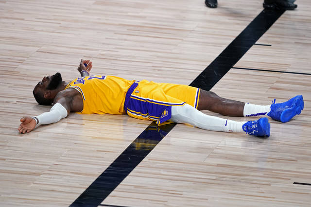Los Angeles Lakers forward LeBron James (23) lies on the court after committing a foul during the second half of an NBA basketball game against the Portland Trail Blazers Tuesday, Aug. 18, 2020, in Lake Buena Vista, Fla. (AP Photo/Ashley Landis, Pool)