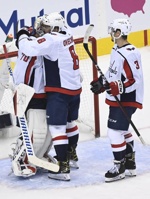 Washington Capitals left wing Alex Ovechkin (8) celebrates his teams win with goalie Braden Holtby (70) after defeating the New York Islanders in an NHL Eastern Conference Stanley Cup playoff hockey game in Toronto, Ontario, on Tuesday, Aug. 18, 2020. (Nathan Denette/The Canadian Press via AP)