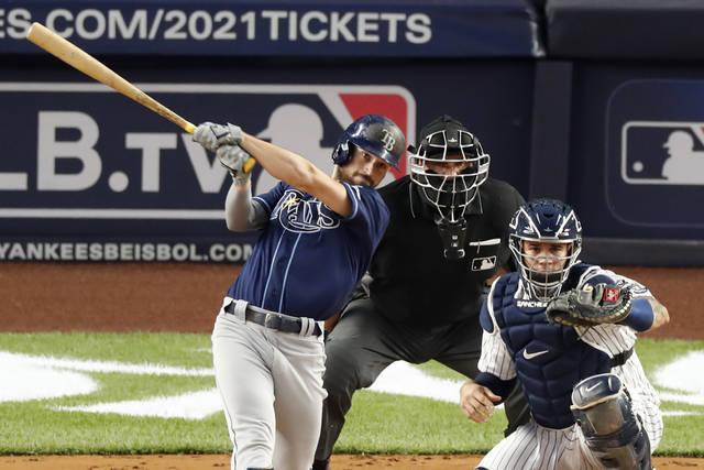 Tampa Bay Rays Brandon Lowe follows through on his third-inning, three-run home run in a baseball game against the New York Yankees, Tuesday, Aug. 18, 2020, in New York. Yankees catcher Gary Sanchez, right, and home plate umpire Chad Fairchild watch from behind the plate. (AP Photo/Kathy Willens)