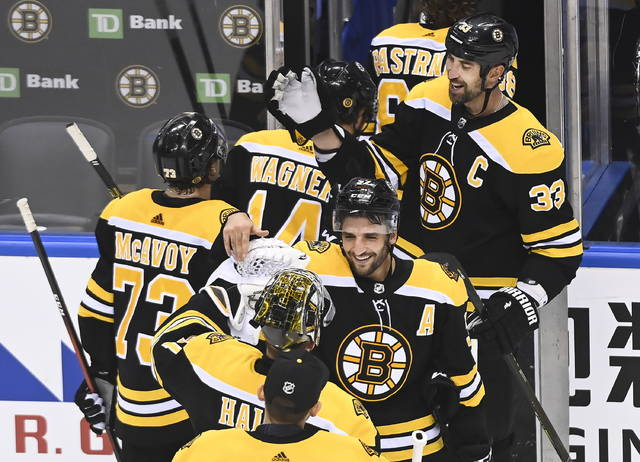 Boston Bruins defenseman Zdeno Chara (33) and Bruins center Patrice Bergeron (37) celebrate with teammates after eliminating the Carolina Hurricanes during third period NHL Eastern Conference Stanley Cup playoff hockey action in Toronto on Wednesday, Aug. 19, 2020. (Nathan Denette/The Canadian Press via AP