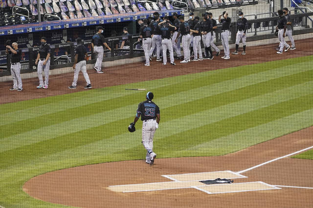 Miami Marlins center fielder Lewis Brinson walks away from home plate after placing a Black Lives Matter T-shirt on home plate as his teammates and the New York Mets walk off the field Thursday, Aug. 27, 2020, in New York. The Mets and Marlins jointly walked off the field after a moment of silence as they chose not to start their scheduled baseball game Thursday night. (AP Photo/John Minchillo)
