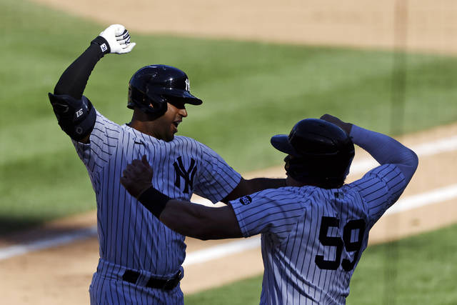 New York Yankees' Aaron Hicks celebrates with Luke Voit (59) after hitting a two-run home run against the New York Mets during the seventh inning of the first baseball game of a doubleheader, Sunday, Aug. 30, 2020, in New York. (AP Photo/Adam Hunger)