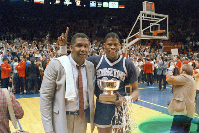 """CORRECTS THAT THE GAME WAS AGAINST ST. JOHNS FOR THE BIG EAST CHAMPIONSHIP, NOT AGAINST HOUSTON FOR THE NCAA CHAMPIONSHIP - FILE - In this March 9, 1985, file photo, Georgetown NCAA college basketball head coach John Thompson poses with player Patrick Ewing after Georgetown defeated St. John's in the Big East Championship in New York.  John Thompson, the imposing Hall of Famer who turned Georgetown into a """"Hoya Paranoia"""" powerhouse and became the first Black coach to lead a team to the NCAA men's basketball championship, has died. He was 78 His death was announced in a family statement Monday., Aug. 31, 2020. No details were disclosed.(AP Photo/File)"""