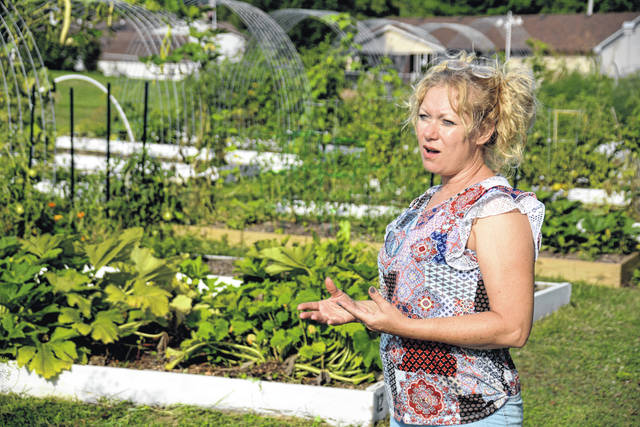 Cassi DeHart provides a Community Garden update for WC Interim President Erika Goodwin and Sigrid Solomon, vice president for student affairs, on a pleasant early August evening.