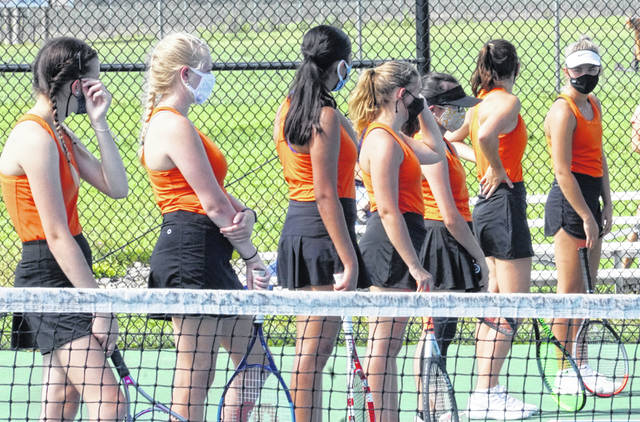 Members of the Wilmington High School tennis team don their masks for pre-match introductions during competition this week against Clinton-Massie. During actual match play, players do not wear the masks. During changeovers, players on each team were observing social distancing requirements with the help of cones on the court.