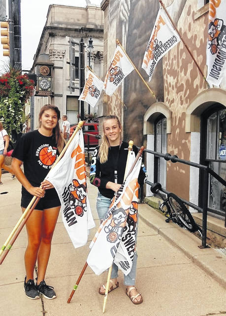 Wilmington High School cheerleaders Breanna Barnett, left, and Elizabeth Custis were downtown early Friday morning to help the community get into the spirit of Hurricane football as the team is set to host East Clinton in Friday night's opener. The teams hope to get the game in as the remnants of one of Mother Nature's hurricanes threatened Southwest Ohio. All tickets for the game were via pre-sale earlier this week, with no tickets available at the gate Friday night due to limitations caused by the pandemic.