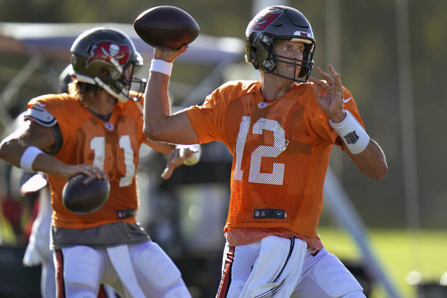 FILE - In this Aug. 24, 2020, file photo, Tampa Bay Buccaneers quarterback Tom Brady (12) and quarterback Blaine Gabbert (11) throw passes during an NFL football training camp practice in Tampa, Fla. No one is traveling more of a distance, at least achievement-wise, than Brady. When it comes to meaningfulness, though, the conversation begins and ends with the six-time Super Bowl champ. At 43, when most football players are looking for tee times, not touchdowns, Brady joins the perennial underachieving Buccaneers. (AP Photo/Chris O'Meara, File)