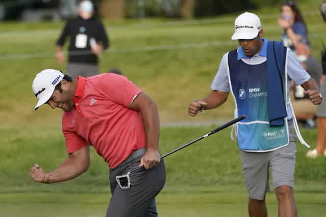 Jon Rahm, left, reacts after making his putt on the first playoff hole next to caddie Adam Hayes during the final round of the BMW Championship golf tournament at the Olympia Fields Country Club in Olympia Fields, Ill., Sunday, Aug. 30, 2020. (AP Photo/Charles Rex Arbogast)