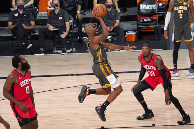 Oklahoma City Thunder's Chris Paul (3) goes up for a shot between Houston Rockets' James Harden (13) and Robert Covington (33) during the second half of an NBA first-round playoff basketball game, Monday, Aug. 31, 2020, in Lake Buena Vista, Fla. (AP Photo/Mark J. Terrill)