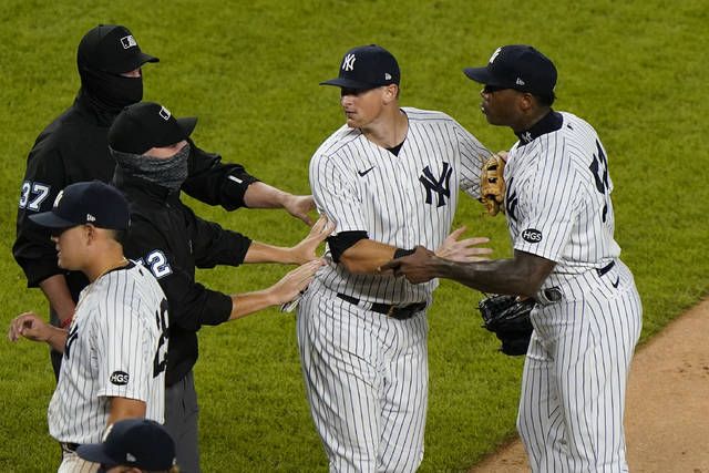 Officials and New York Yankees' DJ LeMahieu restrain New York Yankees relief pitcher Aroldis Chapman, right, after he and the Tampa Bay Rays exchanged words at the end of a baseball game, Tuesday, Sept. 1, 2020, at Yankee Stadium in New York. The incident occurred after Chapman threw a high pitch at the Rays' Michael Brosseau in the ninth inning. (AP Photo/Kathy Willens)