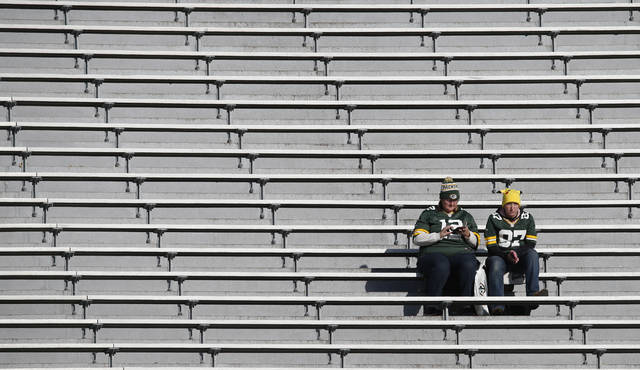FILE - Two fans are shown in the stands before an NFL football game between the Green Bay Packers and the Baltimore Ravens Sunday, Nov. 19, 2017, at Lambeau Field in Green Bay, Wis. Businesses near NFL stadiums have been hit hard due to pandemic-imposed attendance restrictions this season. (AP Photo/Mike Roemer, File)