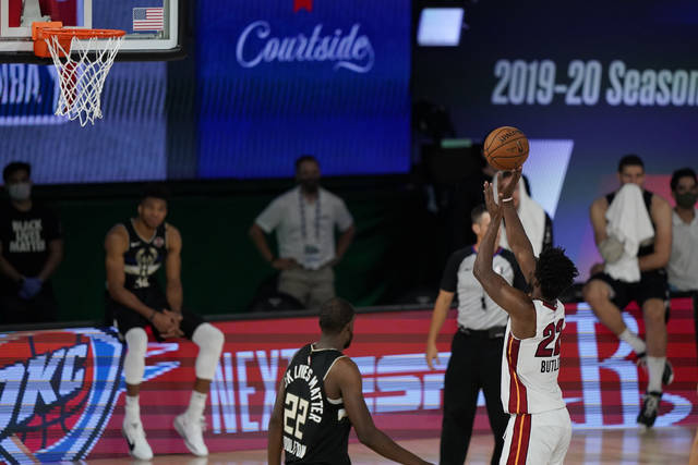 Miami Heat's Jimmy Butler (22) makes a free throw during the second half of an NBA conference semifinal playoff basketball game against the Milwaukee Bucks, Wednesday, Sept. 2, 2020, to give the Heat a 116-114 win over the Milwaukee Bucks in Lake Buena Vista, Fla. (AP Photo/Mark J. Terrill)