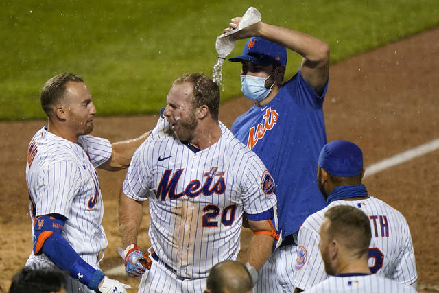 Teammates douse New York Mets' Pete Alonso (20) after Alonso hit a walkoff two-run home run during the 10th inning of a makeup baseball game against the New York Yankees at Citi Field, Thursday, Sept. 3, 2020, in New York. Mets' Brandon Nimmo, left, looks on. (AP Photo/Kathy Willens)