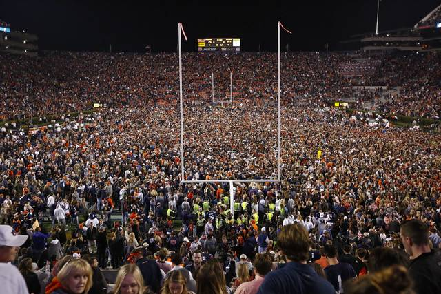 FILE - Fans rush the field after Auburn defeated Alabama in the Iron Bowl NCAA college football game, Saturday, Nov. 25, 2017, in Auburn, Ala. What is most commonly referred to as major college football (aka NCAA Division I Bowl Subdivision or FBS) is compromised of 130 teams and 10 conferences. Seventy-seven of those teams are scheduled to play throughout the fall, starting at various times in September. The other 53, including the entire Big Ten and Pac-12, have postponed their seasons and are hoping to make them up later. That means no No. 2 Ohio State, No. 7 Penn State, No. 9 Oregon and six other teams that were ranked in the preseason AP Top 25. (AP Photo/Brynn Anderson, File)