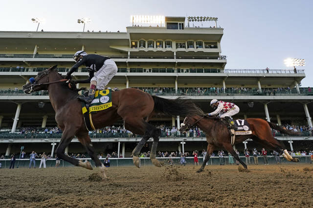 Jockey John Velazquez riding Authentic, right, crosses the finish line ahead of Jockey Manny Franco riding Tiz the Law to win the 146th running of the Kentucky Derby at Churchill Downs, Saturday, Sept. 5, 2020, in Louisville, Ky. (AP Photo/Jeff Roberson)