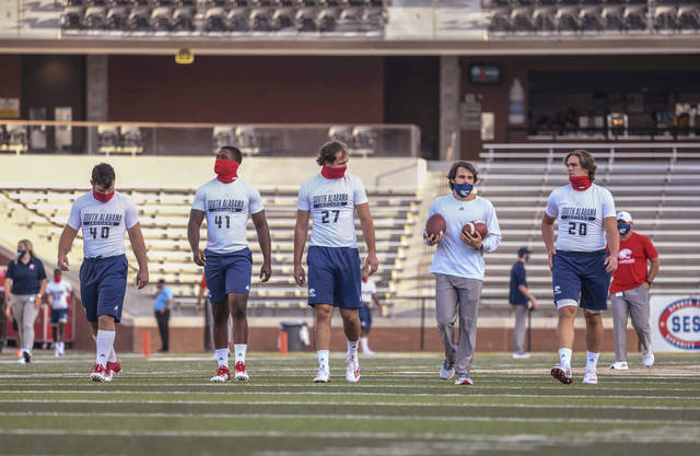 South Alabama players wear masks before an NCAA college football game against Southern Mississippi in Hattiesburg, Miss., Thursday, Sept. 3, 2020. (Cam Bonelli/Hattiesburg American via AP)