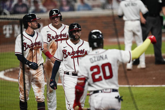 Atlanta Braves' Dansby Swanson, left, Ender Inciarte, center, and Austin Riley return to the dugout after scoring in a double by Ronald Acuna Jr. during the sixth inning of a baseball game against the Miami Marlins on on Wednesday, Sept. 9, 2020, in Atlanta. (AP Photo/Brynn Anderson)