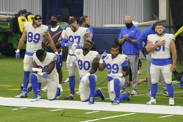 Members of the Los Angeles Rams stand and kneel during the national anthem before an NFL football game against the Dallas Cowboys Sunday, Sept. 13, 2020, in Inglewood, Calif. (AP Photo/Ashley Landis)