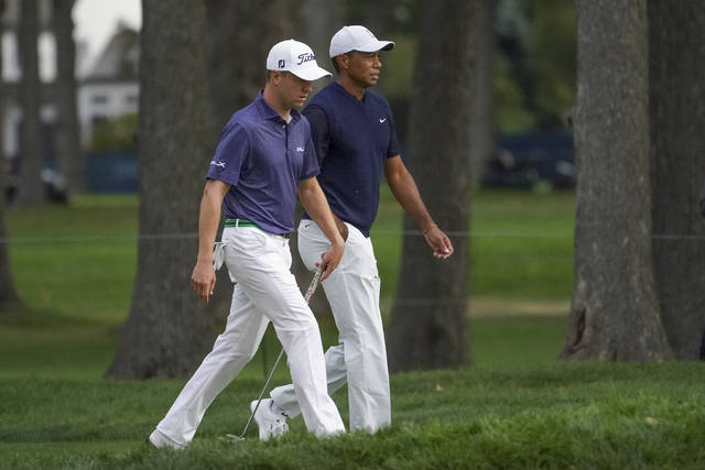 Justin Thomas, of the United States, left, and Tiger Woods, of the United States, walk up to the seventh green during the first round of the US Open Golf Championship, Thursday, Sept. 17, 2020, in Mamaroneck, N.Y. (AP Photo/John Minchillo)